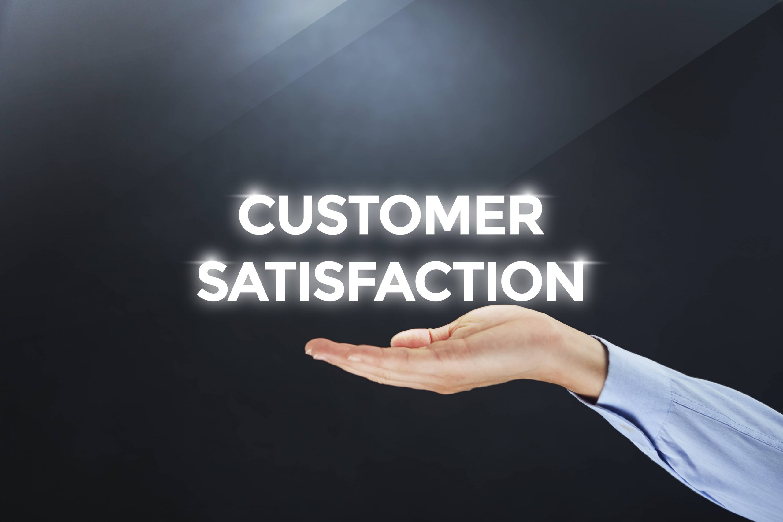 hand is out holding the words customer satisfaction in bright lights